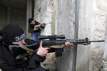 Um Jaafar, a woman fighter in the Free Syrian Army, takes aim with her weapon as she undergoes military training by her husband Abu Jaafar, a Sawt al-Haq battalion commander, in Aleppo