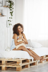 Beautiful african girl in sleepwear smiling holding pillow sitting on bed at home. Copy space.
