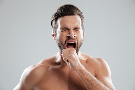 Portrait of a bored beraded man with naked shoulders yawning