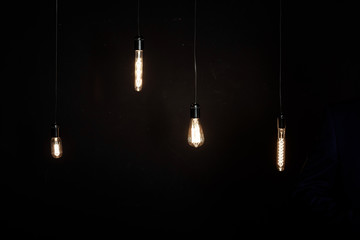Bright glowing light bulbs of different shapes on dark background