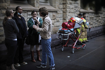 Residents talk near a building that collapsed in Harlem, New York City