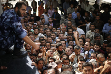 A Palestinian policeman gestures as Hamas-hired civil servants wait to receive a payment in Gaza City