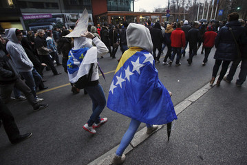Anti-government protesters with Bosnia and Herzegovina national flags draped over themselves, walk in Sarajevo