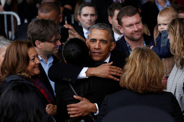 Former president Barack Obama embraces a staff member before boarding Special Air Mission 28000, a Boeing 747 which serves as Air Force One, at Joint Base Andrews, Maryland