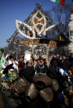 Participant dressed in traditional costume carries her mask during the International Festival of the Masquerade Games in the town of Pernik