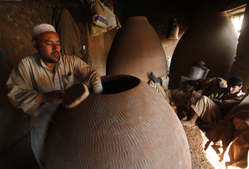 An Afghan man makes a tandoor oven used for making bread in Kabul