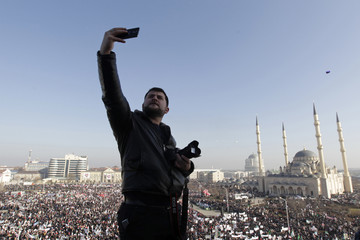 A man takes pictures of himself during a rally to protest against satirical cartoons of prophet Mohammad, in Grozny, Chechnya