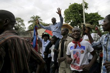 Presidential candidate Moise Jean Charles of Pitit Desalin political platform waves as he is carried by supporters during a rally in Port-au-Prince