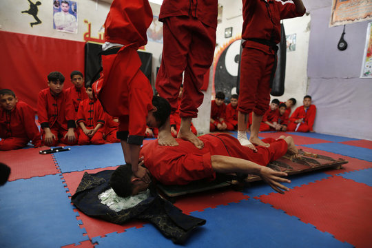 Palestinian boys stand at body of their classmate as he lies on glass and knifes during a class at the Red Dragon martial arts club in Beit Lahiya