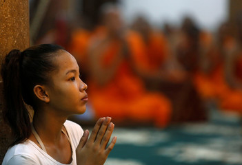 A girl prays at a pagoda during the first day of the Pchum Ben festival in Phnom Penh