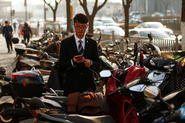 A man in a suit plugs in his mobile phone as he prepares to mount an electric scooter in Beijing