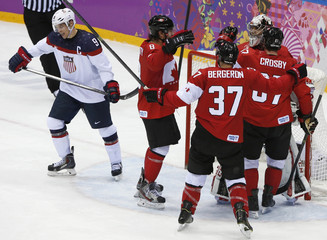 Canada's players celebrate their win as Team USA's Parise skates away during their men's ice hockey semi-final game at the Sochi 2014 Winter Olympic Games