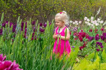 Little girl in pink dress walking through field of flowers