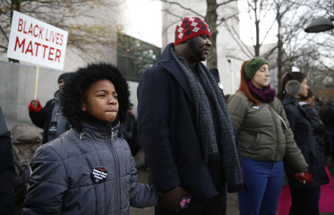 Marchers hold hands during a prayer at the national Justice For All march against police violence, in Washington