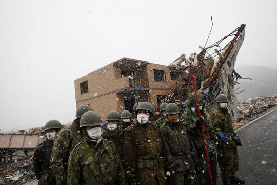 Members of the Japan Self-Defense Force listen to instructions after they arrived at the devastated residential area in Otsuchi as heavy snow falls