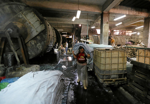 """A labourer works in a leather tannery where Co-founders of a local brand """"Okhtein"""", sisters Aya and Mounaz Abdelraouf purchase leather in Cairo"""