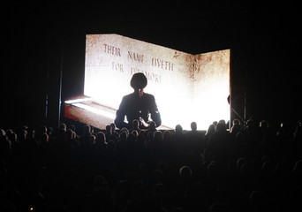 A live view of an honour guard standing in front of a remembrance stone is shown on a giant screen during a dawn memorial service on ANZAC Day at the Australian National War Memorial in Canberra