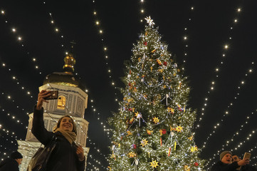 People take pictures next to illuminated Christmas tree in front of St. Sophia Cathedral in central Kiev