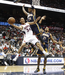 Hawks guard Harris passes the ball under pressure from Pacers George and West in the first half of their first-round Eastern Conference playoff NBA basketball game in Atlanta