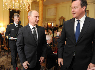 Britain's Prime Minister David Cameron and Russia's President Vladimir Putin take part in a ceremony to award the Russian Ushakov medal to Arctic convoy veterans in 10 Downing Street, central London