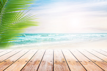 Empty wooden table and palm leaves with party on beach blurred background. Concept Summer, Beach, Sea, Relax, Party.