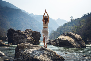 Woman making yoga on a bank of river