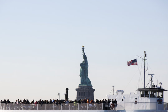 Tourists stand on the deck of a boat as it motors past the Statue of Liberty National Park in New York