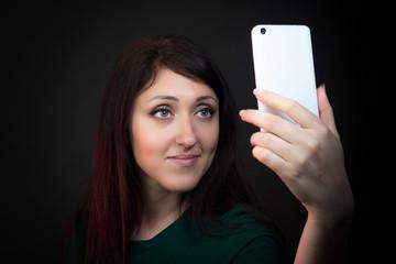 Beautiful young woman making selfie