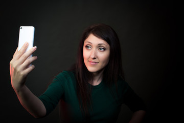 Beautiful young woman making selfie against a dark background