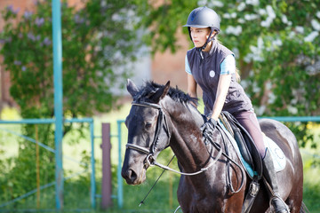 Young rider girl on horse at dressage competition. Equestrian sport background