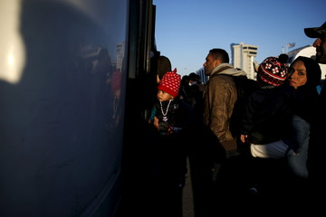 Refugees and migrants board a bus after arriving aboard the passenger ferry Eleftherios Venizelos from the island of Lesbos at the port of Piraeus