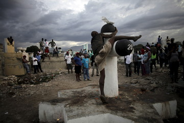 Residents look at a drunk man as he climbs on a Baron Samdi cross, as they wait for the start of a voodoo ceremony, at the cemetery of Croix des Bouquets, on the outskirts of Port-au-Prince