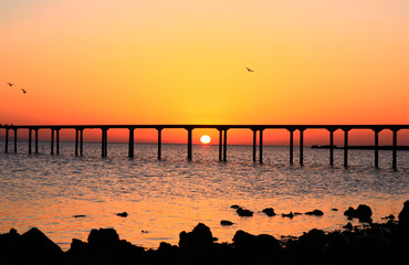 Sunrise landscape, sea with bridge and orange sky background