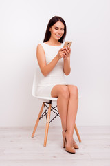 Full size portrait of cute brunette sitting on white chair and texting on the phone. She is typing something with excitement, smiling