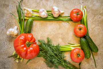 Frame of assorted fresh vegetables on beige cement background with copy space