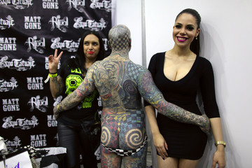 """Matt Gone, also known as """"The Checkered Man"""", poses with women during the """"Expo Tatuaje"""" international, a tattoo expo, in Monterrey"""