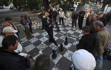 Men play chess in downtown Banja Luka