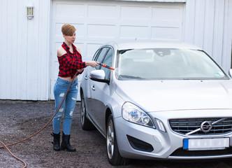 A woman with dark short hair wash a car