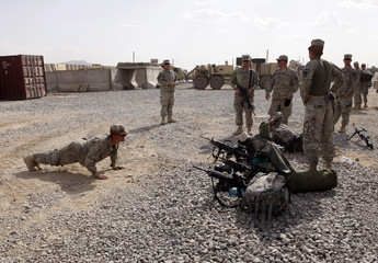 U.S. soldier from 20th Battalion, 584 MAC, Route Clearance Patrol performs push-ups while colleagues watch, on a Forward Operating Base in Kandahar