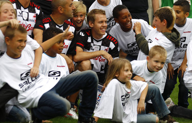 Germany's Red Bull Formula One World Champion Sebastian Vettel pose for a picture with children prior to a charity soccer match in Frankfurt