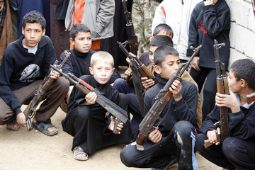 Boys carry weapons during a weapon handover event to the Iraqi government in Basra