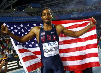 Jason Richardson of the U.S. holds up his flag after taking second place at the men's 110 metres hurdles final in Daegu