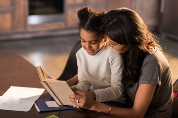 Smiling mother and daughter sitting together at table and reading book, homework help concept