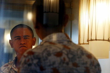 Xiao Jiguo reacts after shaping his eyebrows to impersonate U.S. President Barack Obama in Guangzhou