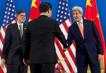 Chinese President Xi Jinping shakes hands with US Secretary of State John Kerry alongside US Secretary of Treasury Jacob Lew