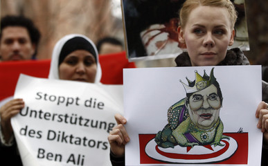 Protesters hold placards while demonstrating against Tunisian President  Ben Ali in Berlin