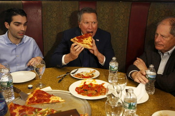 Kasich eats a slice of pizza with Ulrich and Turner at Gino's Pizzeria and Restaurant in the Queens borough of New York