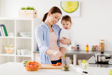 happy mother and baby cooking food at home kitchen