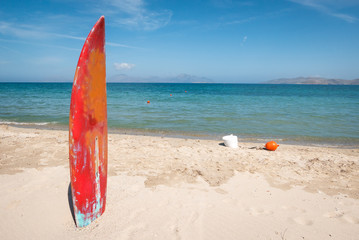 Surfboard stick on sandy beach as a sign of the water sports zone.