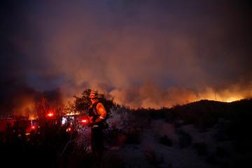 A firefighter watches as smoke clouds billow during the Pilot Fire near Silverwood Lake in San Bernardino county near Hesperia, California